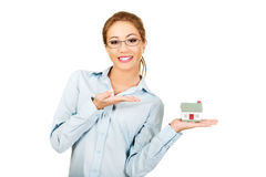 Businesswoman presenting a house model. Stock Image