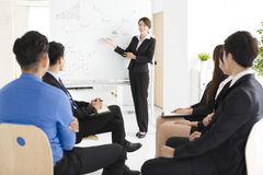 Businesswoman presenting new project to partners in office Stock Image