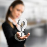 Businesswoman presenting a questionmark as symbol for a concern. In front of an office scene royalty free stock images