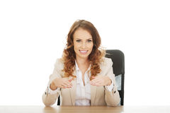 Businesswoman presenting something in hands. Stock Photos