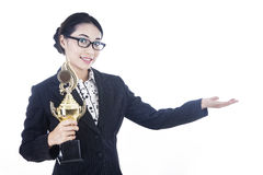 Businesswoman presenting trophy to the winner. A proud businesswoman presenting a trophy to the winner by showing her hand Royalty Free Stock Photography