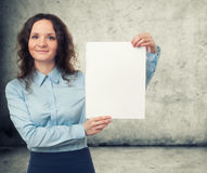 Businesswoman presenting white blank paper sheet Stock Photo