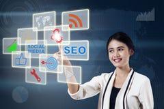Businesswoman pressing an icon Stock Photos