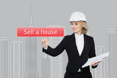 Businesswoman pressing sell a hause button on virtual screens Royalty Free Stock Photo