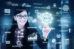 Businesswoman pressing SEO icon. Young Asian businesswoman pressing SEO icon on a virtual screen. Concept of Search Engine Optimization Stock Photo
