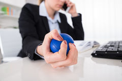 Businesswoman Pressing Stressball At Desk royalty free stock photography