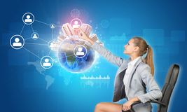 Businesswoman pressing touch screen button on. Virtual interface featuring Globe with buildings on top and network with person icons, on blue background Royalty Free Stock Images