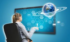 Businesswoman pressing touch screen button on. Virtual interface with Globe and hexagons with icons, on blue background. Element of this image furnished by NASA Stock Images