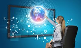 Businesswoman pressing touch screen button on. Virtual interface with Globe and network with people icons, on blue background. Element of this image furnished Stock Images