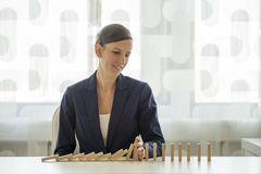 Businesswoman preventing dominoes from crumbling Royalty Free Stock Images