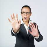 Businesswoman protecting. A portrait of a strict buisnesswoman with a very stressed expresssion on face gesturing like she is protecting oneself Royalty Free Stock Photography