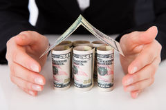 Businesswoman Protecting House Made Of Dollar Bills. Cropped image of businesswoman protecting house made of dollar bills at office desk Royalty Free Stock Image