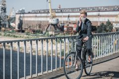 Businesswoman in protective mask riding bicycle on bridge and talking by smartphone air. Pollution concept stock photo