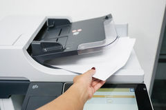 Businesswoman pull paper from the printer. Businesswoman pull pieces of paper from the printer Stock Photos