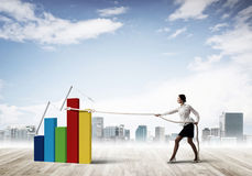 Businesswoman pulling arrow with rope and making it raise up Stock Photography