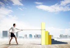 Businesswoman pulling arrow with rope and making it raise up Royalty Free Stock Image