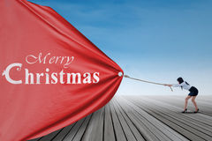 Businesswoman pulling big christmas banner Royalty Free Stock Image