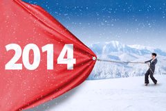 Businesswoman pulling big number of 2014. Asian businesswoman is pulling big number of 2014 on snow mountain stock photo