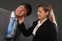 Businesswoman pulling a businessman ear. A hand pulling a businessman ear on gray Royalty Free Stock Image
