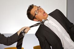 Businesswoman pulling businessman by tie Stock Image