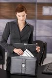 Businesswoman pulling contract from briefcase Royalty Free Stock Photos
