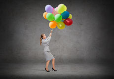 Businesswoman pulling down bunch of balloons Stock Photos