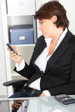 Businesswoman pulling a face at a text message Stock Images