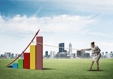 Businesswoman pulling graph with rope as concept of power and control Royalty Free Stock Image