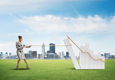 Businesswoman pulling graph with rope as concept of power and control Royalty Free Stock Photography
