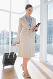 Businesswoman pulling her suitcase and checking her phone Stock Photo