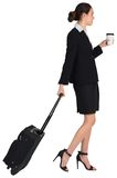 Businesswoman pulling her suitcase holding coffee Stock Photography
