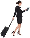 Businesswoman pulling her suitcase holding tablet Royalty Free Stock Photos