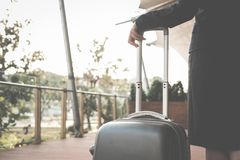 businesswoman pulling luggage outdoors. woman carrying baggage f Stock Photos