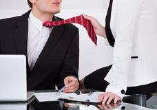 Businesswoman pulling male colleague's tie while seducing him Royalty Free Stock Photo