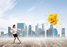 Businesswoman pulling paper ball with rope and making it raise up Royalty Free Stock Photos