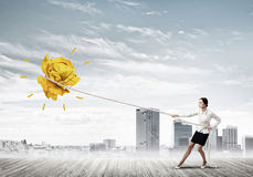 Businesswoman pulling paper ball with rope and making it raise up Royalty Free Stock Photography
