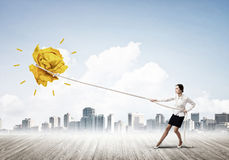 Businesswoman pulling paper ball with rope and making it raise up Stock Photos