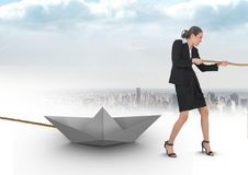 Businesswoman pulling paper boat with rope in city Royalty Free Stock Photography