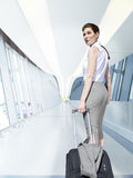 Businesswoman pulling rolling luggage in airport concourse Stock Photography