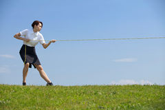 Businesswoman pulling rope in park Royalty Free Stock Photography