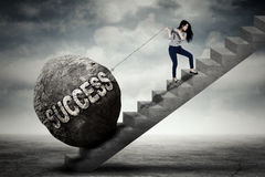Businesswoman pulling success word on stair. Image of young businesswoman pulling a boulder with success word while climbing on the stair Stock Image