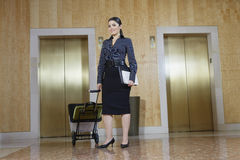Businesswoman Pulling Trolley Against Elevators Stock Photo