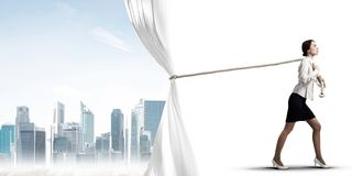 Young woman opening white curtain and presenting modern city landscape Royalty Free Stock Photos