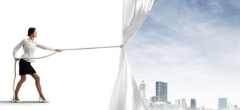 Young woman opening white curtain and presenting modern city landscape Stock Photo