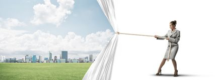 Young woman opening white curtain and presenting modern city landscape Stock Images