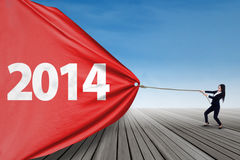 Businesswoman pulls banner of new year 2014 Royalty Free Stock Photo