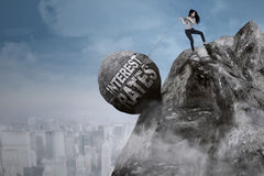 Businesswoman pulls boulder on the cliff Stock Photos
