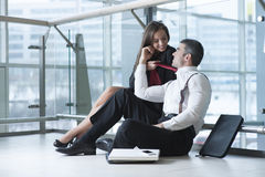 Businesswoman pulls male coworker towards her with his tie Stock Photo
