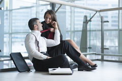 Businesswoman pulls male coworker towards her with his tie Royalty Free Stock Photos