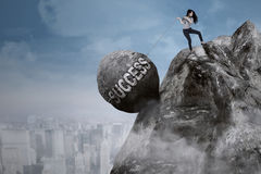 Businesswoman pulls success word on the cliff. Young Asian businesswoman is pulling big rock with success word while climbing on the cliff Royalty Free Stock Images